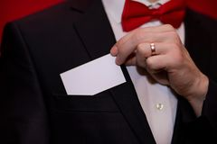 Homme élégant dans la carte de visite professionnelle de visite blanche de prise de costume sur le fond rouge, foyer sur la carte Photographie stock libre de droits