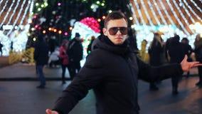 Homme élégant dans la danse drôle en verre à une partie à la nouvelle année sur l'arbre de Noël de ville banque de vidéos