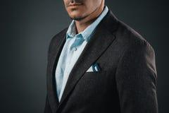 Homme élégant dans le costume d'isolement sur le gris image libre de droits