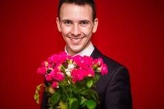 Homme élégant dans le costume tenant un bouquet des fleurs avec le fond rouge Photo libre de droits
