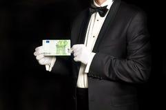 Homme élégant dans le smoking tenant le billet de banque de l'euro 100 Photographie stock libre de droits