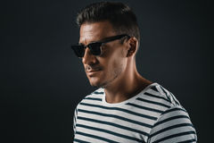 Homme élégant dans le T-shirt rayé et des lunettes de soleil, d'isolement sur le gris photographie stock libre de droits