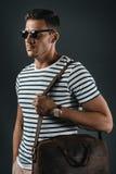 Homme élégant dans le T-shirt rayé et des lunettes de soleil tenant le sac en cuir, photographie stock