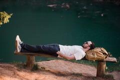 Homme élégant de randonneur se trouvant sur un banc en bois près du lac Images libres de droits