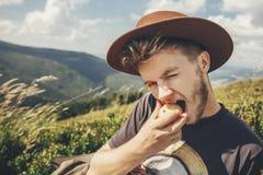 Homme élégant de voyageur dans le chapeau mangeant la pomme sur le mountai ensoleillé images stock