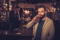 Homme élégant gai avec une pinte de bière pression au compteur de barre dans le bar Image stock