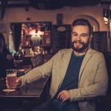 Homme élégant gai avec une pinte de bière pression au compteur de barre dans le bar Photos stock