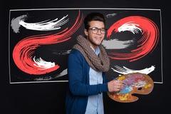 Homme élégant heureux tenant la palette et la peinture Photo stock