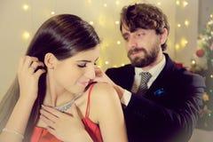 Homme élégant mettant le cadeau de collier à la nuit de Noël d'amie heureuse Images libres de droits