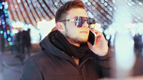Homme élégant parlant au téléphone la nuit de Noël près de l'arbre principal de nouvelle année de ville, une réflexion des lumièr banque de vidéos