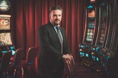Homme élégant près des machines à sous dans un intérieur de luxe de casino Photos libres de droits