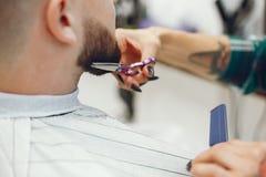 Homme élégant s'asseyant dans un raseur-coiffeur images stock