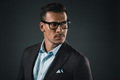 Homme élégant sûr dans des lunettes regardant loin d'isolement sur le gris photographie stock