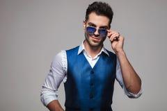 Homme élégant souriant et fixant ses lunettes de soleil bleues Images libres de droits