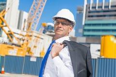 Homme élégant supérieur de constructeur dans le costume au chantier de construction le jour ensoleillé d'été Photographie stock