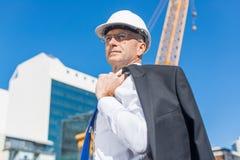 Homme élégant supérieur de constructeur dans le costume au chantier de construction le jour ensoleillé d'été Image libre de droits