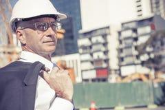 Homme élégant supérieur de constructeur dans le costume au chantier de construction sur ensoleillé Photo libre de droits