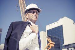 Homme élégant supérieur de constructeur dans le costume au chantier de construction sur ensoleillé Images stock