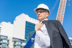 Homme élégant supérieur de constructeur dans le costume au chantier de construction le jour ensoleillé d'été Photographie stock libre de droits