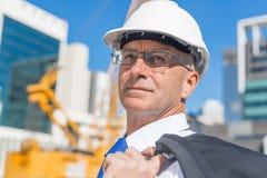Homme élégant supérieur de constructeur dans le costume au chantier de construction le jour ensoleillé d'été Photos stock
