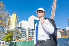 Homme élégant supérieur de constructeur dans le costume au chantier de construction le jour ensoleillé d'été Images stock