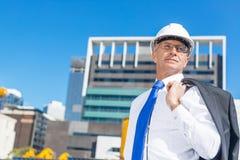 Homme élégant supérieur de constructeur dans le costume au chantier de construction le jour ensoleillé d'été Images libres de droits