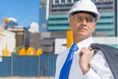 Homme élégant supérieur de constructeur dans le costume au chantier de construction le jour ensoleillé d'été Image stock