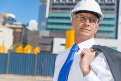 Homme élégant supérieur de constructeur dans le costume au chantier de construction le jour ensoleillé d'été Photo stock