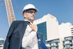 Homme élégant supérieur de constructeur dans le costume au chantier de construction sur ensoleillé Images libres de droits