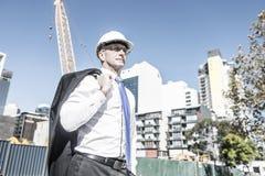 Homme élégant supérieur de constructeur dans le costume au chantier de construction sur ensoleillé Photo stock