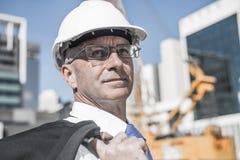 Homme élégant supérieur de constructeur dans le costume au chantier de construction sur ensoleillé Photos stock