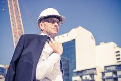 Homme élégant supérieur de constructeur dans le costume au chantier de construction sur ensoleillé Photographie stock libre de droits