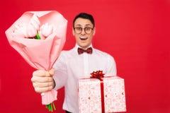 Homme élégant, verres de port, avec un cadeau et un bouquet des fleurs, sur un fond rouge, le concept du jour des femmes images stock