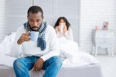 Homme émotif fatigué s'asseyant avec une tasse près de son épouse photo stock
