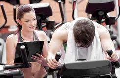 Homme épuisé faisant des exercices avec son entraîneur Photographie stock