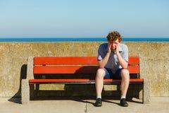 Homme épuisé fatigué s'asseyant sur le banc par l'océan de mer Photo libre de droits