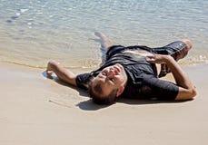 Homme épuisé se trouvant sur la plage photo stock