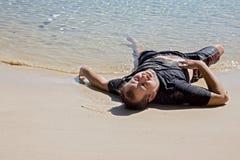 Homme épuisé se trouvant sur la plage de mer images libres de droits