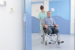 Homme étant enfoncé le fauteuil roulant par l'infirmière Image stock