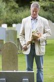 Homme étendant des fleurs sur la tombe Photo stock