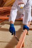 Homme étendant la couche d'isolation thermique sur le bâtiment Photos stock