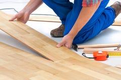 Homme étendant le plancher en stratifié Photographie stock