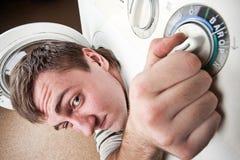 Homme étonné à l'intérieur de machine à laver Photographie stock libre de droits