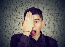 Homme étonné avec beaucoup d'ampoules d'idée de questions et réponses couvrant la moitié de son visage de main Images stock