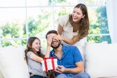 Homme étonné avec le cadeau dans le sofa Image libre de droits