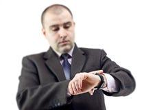 Homme étonné d'affaires consultant le sien montre Photos stock