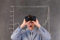 Homme étonné regardant par des jumelles sur le fond avec l'infographics photographie stock libre de droits
