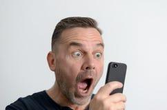 Homme étonné regardant son téléphone portable Image stock
