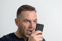 Homme étonné regardant son téléphone portable Images libres de droits
