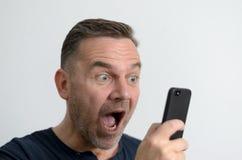 Homme étonné regardant son téléphone portable Photo stock